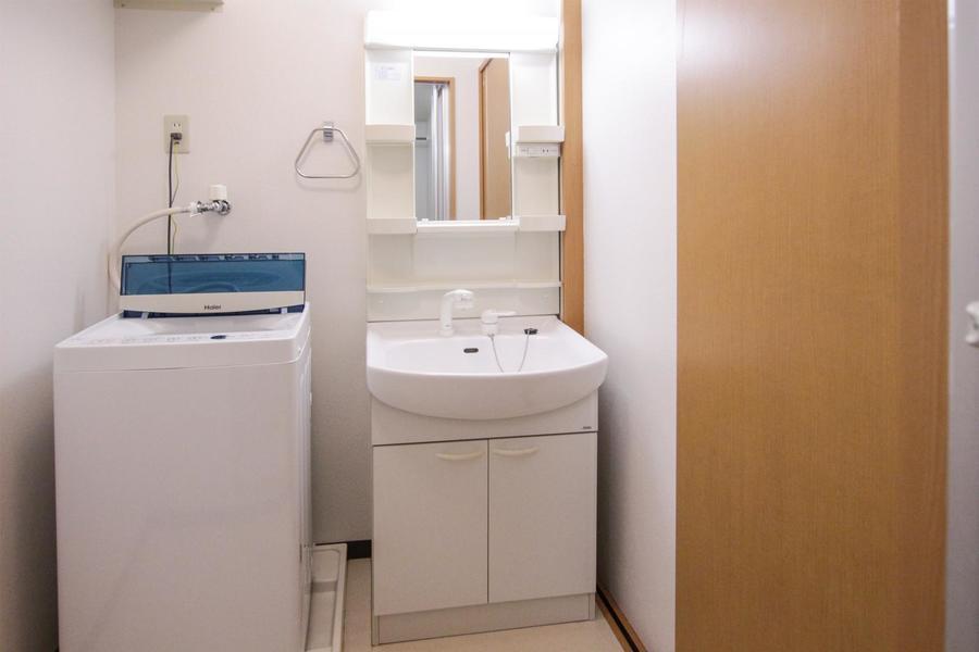 洗面台は大きな鏡と小物置き場が特徴。コンセント口も搭載されています