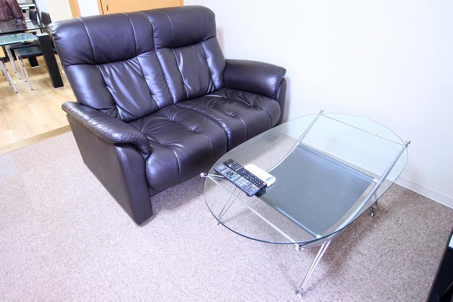 革張りソファとガラステーブルの組み合わせはクールな印象