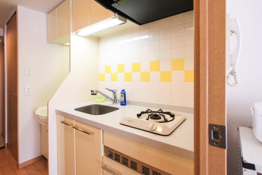 ホワイト×イエローのタイルワークが鮮やか。元気の出るキッチンです