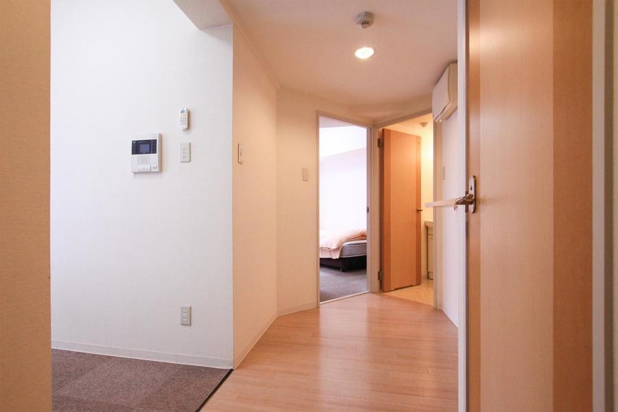 玄関周辺は白と木目調の扉で統一されあたたかな印象を与えます