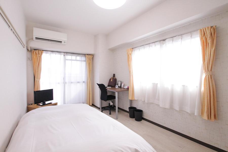グレージュ系のフローリングと白い壁紙のシンプルで過ごしやすいお部屋