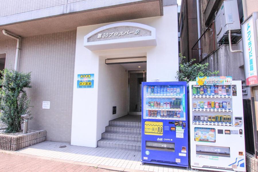 玄関先には自動販売機が設置。近隣にはコンビニもあり便利です