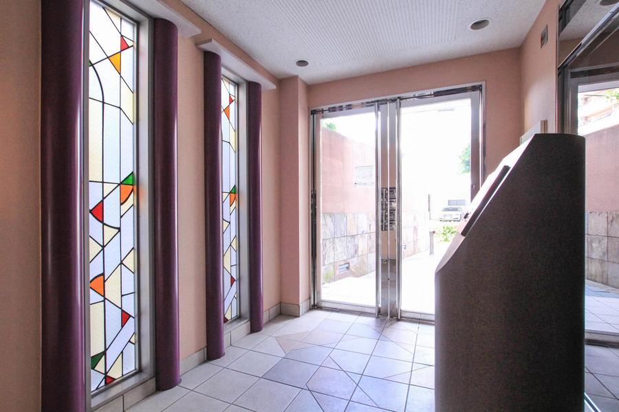 シンプルなエントランスにはステンドグラス調の飾り窓が華を添えます
