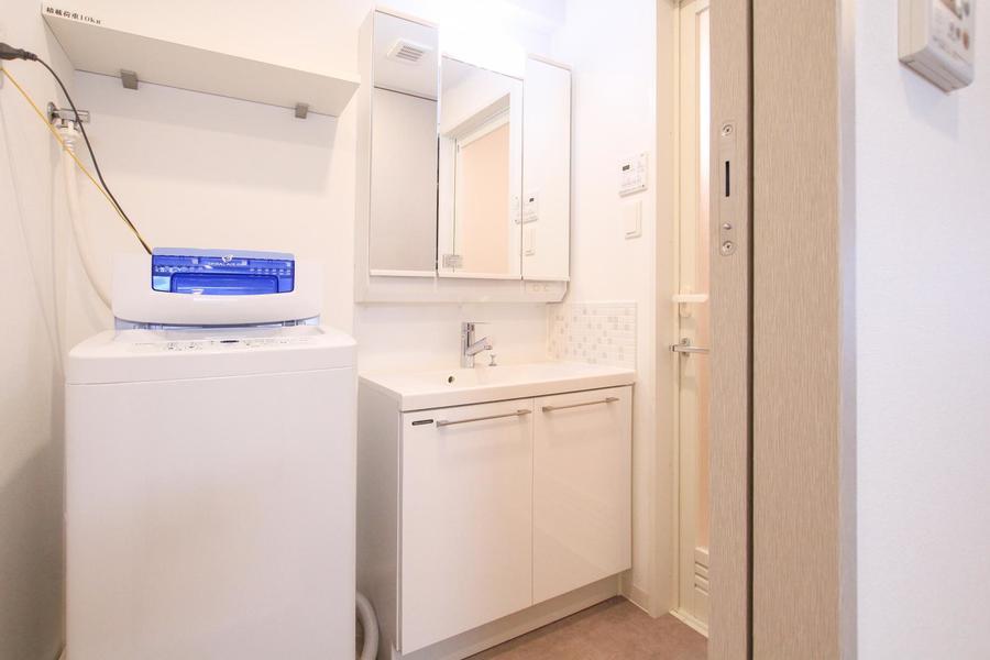 全面鏡の扉が特徴の洗面台。裏は収納スペースで小物類もすっきり