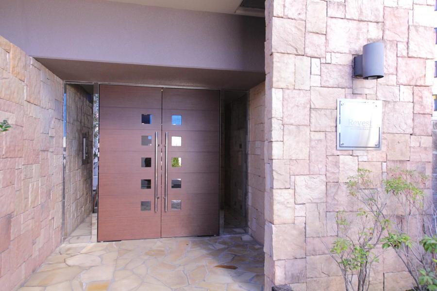 四角い石を組み合わせたエントランス。木製のドアがあたたかみをプラス