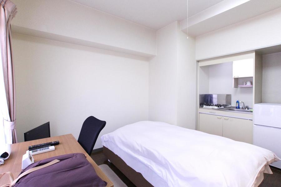 ベッドを中心にデスク、テレビ、冷蔵庫など手の届く範囲に設置されています