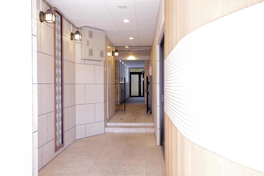 シンプルなエクステリアの中、アンティーク風のランプや扉が光ります