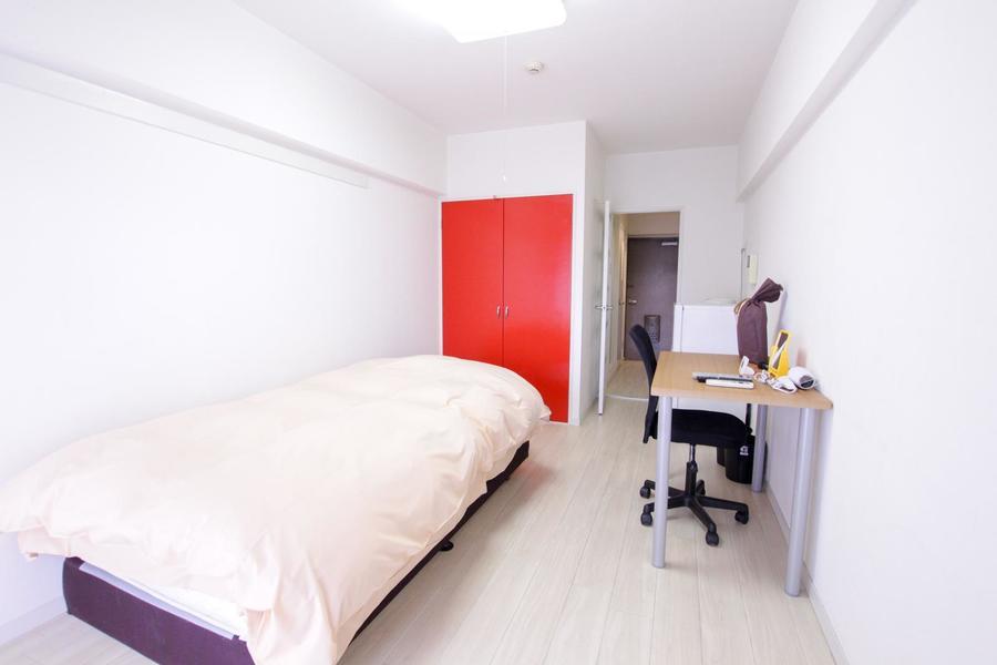 シンプルかつコンパクトなお部屋。クローゼットの扉の赤が目を引きます