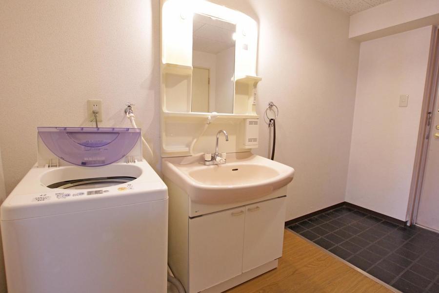 洗面台は大きな鏡が特徴。小物置きの棚もあり置き場に困りません
