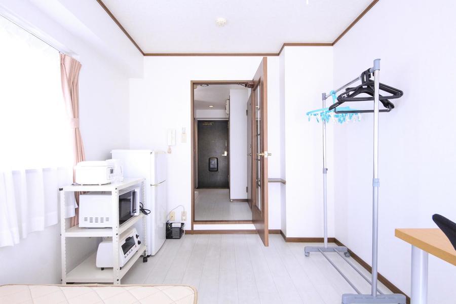 白の壁紙にダークブラウンの扉や梁がパイピングのようなアクセントに